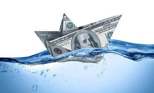 Image of a paper boat made of money sitting in water.